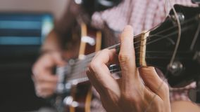 Den manliga musikern spelar gitarren, räcker tätt upp, fokusen på gitarrfretboarden Royaltyfri Bild