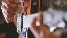 Den manliga musikern spelar gitarren, räcker tätt upp, fokusen på gitarrfretboarden Arkivbild