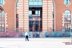Den manliga ordningsvakten går runt om byggnaden som det skyddar arkivbilder