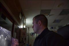 Den manliga ordningsvakten på arbetsplats ser låg ligth för bildskärmen royaltyfri bild