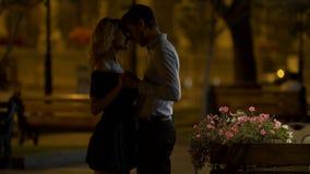 Den manliga parkerar älskar hållande flickvännens hand och att krama henne, aftondatum i stad, lager videofilmer