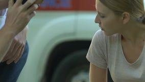 Den manliga passerbyen som kallar 911, understödjande barn, sårade kvinnligt sammanträde på vägen arkivfilmer