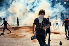 Den manliga personen som protesterar som kör i väg från tårgasröken som avfyras av polisen under Gezi, parkerar protester i Ankar arkivfoton