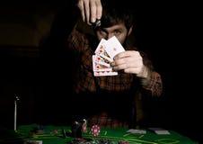 Den manliga pokerspelaren rymmer fem kort, vinnande kombination På en mörk bakgrund Arkivfoto