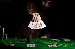 Den manliga pokerspelaren rymmer fem kort, vinnande kombination På en mörk bakgrund Royaltyfri Fotografi
