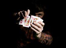 Den manliga pokerspelaren rymmer fem kort, vinnande kombination På en mörk bakgrund Arkivfoton