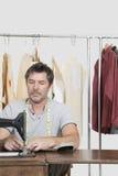Den manliga sömmerskan som syr torkduken på symaskinen med kläder, rack i bakgrund Arkivbild