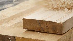 Den manliga snickaren kontrollerar kvaliteten av brädena Man som arbetar på en wood hyvla maskin långsam rörelse arkivfilmer