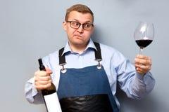 Den manliga sommelieren är kontrollera och testa rött vin royaltyfria bilder
