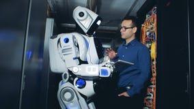 Den manliga specialisten förklarar till en cyborg vad som ska göras med plugga-i serveror lager videofilmer