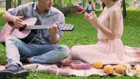 Den manliga spela gitarren och den sjungande sången med flickvännen parkerar picknicken, vänner vilar arkivfilmer