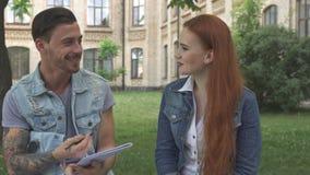 Den manliga studenten noterar vad hans klasskompis säger royaltyfria bilder