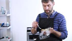 Den manliga stylisten har en lunch på arbetsplatsen, stilig grabb med lunchboxen lager videofilmer