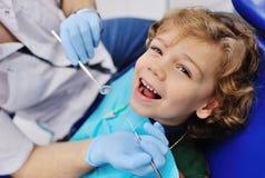 Den manliga tandläkaren undersöker en ung patient arkivbilder