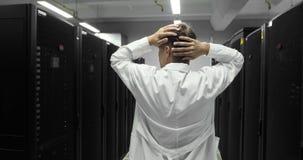 Den manliga IT-teknikeren klamra sig fast intill hans huvud Problem med serveren en hackerattack i stora Dara Center lager videofilmer