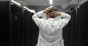 Den manliga IT-teknikeren klamra sig fast intill hans huvud Problem med serveren en hackerattack i stora Dara Center arkivfilmer