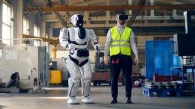 Den manliga teknikern bär VR-exponeringsglas och styrning en cyborg lager videofilmer