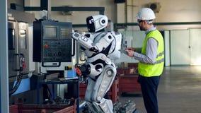 Den manliga teknikern klarar av en cyborg med hans dator lager videofilmer