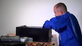 Den manliga teknikerteknikermannen tar bort PCmoderkortet från svart fall lager videofilmer