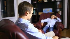 Den manliga terapeuten för en psykologisk konsultation med en tonåring Pojketonåring på mottagandet av a lager videofilmer