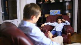 Den manliga terapeuten för en psykologisk konsultation med en tonåring Pojketonåring på mottagandet av a arkivfilmer