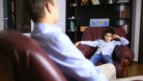 Den manliga terapeuten för en psykologisk konsultation med en tonåring Pojketonåring på mottagandet av a stock video