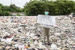 Den manliga tonåringen rymmer plast- föroreningtext för stoppet royaltyfria foton