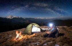 Den manliga turisten har en vila i hans läger på natten under härlig himmel mycket av stjärnor och den mjölkaktiga vägen arkivbild