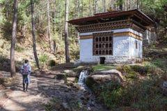 Den manliga turisten i bhutanesisk klänning går passerandevattenkraftbönen royaltyfri foto