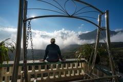 Den manliga turisten sitter på balkong som ser berglandskap med låga vita moln under briljant himmel Idéer för lopp och känsla arkivfoto