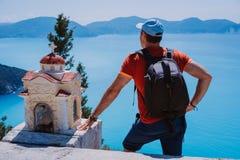 Den manliga turisten som blir nära den lilla hellenska relikskrin Proskinitari, beundrar landskap för havskustlinjeform Fantastis arkivbild