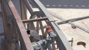 Den manliga welderen fungerar, genom att svetsa med metallkonstruktion och knackar lätt på den med en järnhammare stock video