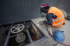 Den manliga welderen svetsar den nya stålspisgallret, bågsvetsningprocess med gnistor Industriarbetarebegrepp exponering long royaltyfria foton