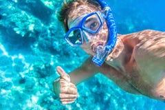 Den Mann schnorcheln, der unter Wasser Daumen aufgibt Lizenzfreie Stockfotos