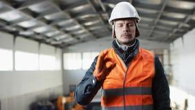 Den manskägget och mustaschen i en hård hatt och overaller står i mitt av hangaren, och alla uppvisning är ok på