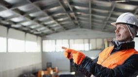 Den manskägget och mustaschen i en hård hatt och overaller står i mitt av hangaren och dansar på kameran