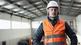 Den manskägget och mustaschen i en hård hatt och overaller står i mitt av hangaren och ser hans armbandsur