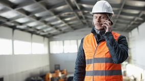 Den manskägget och mustaschen i en hård hatt och overaller står i mitt av hangaren och talar vid hans telefon på