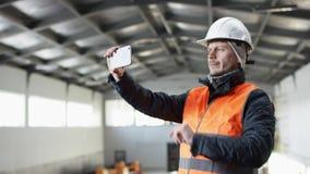 Den manskägget och mustaschen i en hård hatt och overaller står i mitt av hangaren och tar fotoet på hans telefon