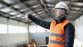 Den manskägget och mustaschen i en hård hatt och overaller står i mitt av hangaren och tar på foto av hjälpmedel