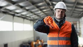 Den manskägget och mustaschen i en hård hatt och overaller står i mitt av hangaren och tummarna ner på kameran
