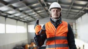 Den manskägget och mustaschen i en hård hatt och overaller står i mitt av hangaren och visar drillborren på