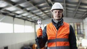 Den manskägget och mustaschen i en hård hatt och overaller står i mitt av hangaren och visar den justerbara skiftnyckeln