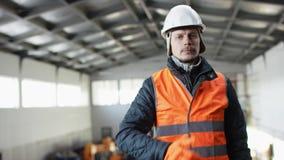Den manskägget och mustaschen i en hård hatt och overaller står i mitt av hangaren och visar upp tummar på