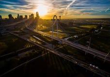 Den Margaret Hunt Hill Bridge Sunrise Dallas Texas Skyline Downtown Cityscape Sunrise solen rays över Urban Prawl den massiva sta royaltyfri bild