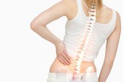 Den markerade ryggen av kvinnan med tillbaka smärtar Arkivfoto