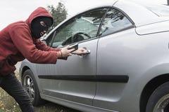 Den maskerade banditen öppnar det centrala låset av en dyr modern bil med hjälpen av en mobiltelefon Förbind till MirrorLink arkivbilder