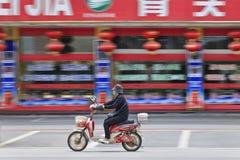 Den maskerade mannen på e-cykeln passerar en restaurang, Shanghai, Kina Fotografering för Bildbyråer
