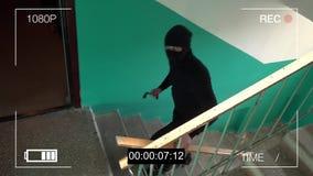 Den maskerade rånaren bryter att ta bort bevakningkameramonteringen stock video