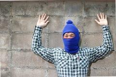 Den maskerade tjuven lyftte armar med bakgrund för tegelstenväggen Låsinbrottstjuvbegrepp fotografering för bildbyråer